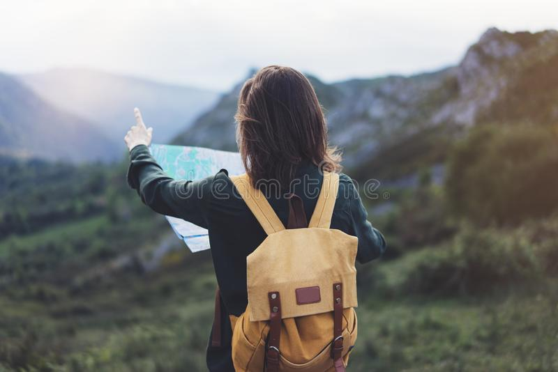Hipster young girl with backpack enjoying sunset on peak of foggy mountain, looking a map and poining hand. Tourist traveler. On background valley landscape royalty free stock photography