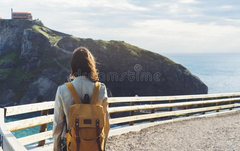 Hipster young girl with backpack enjoying sunset on seascape on peak mountain. Tourist traveler on background valley landscape. View mockup. Hiker looking ocean royalty free stock photos