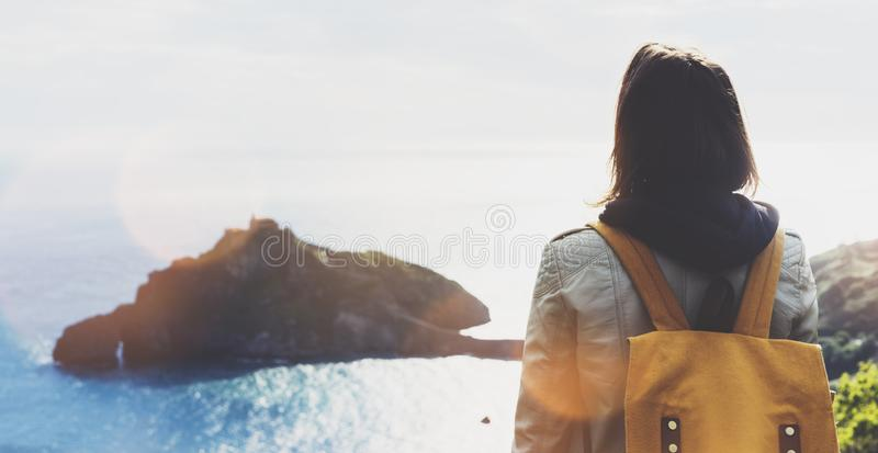 Hipster young girl with backpack enjoying sunset on seascape on peak mountain. Tourist traveler on background valley landscape. View mockup. Hiker looking royalty free stock photo