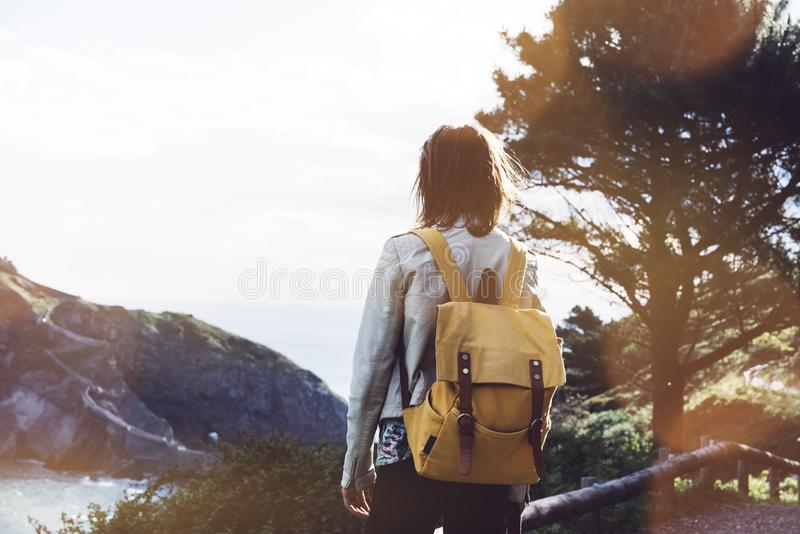 Hipster young girl with backpack enjoying sunset on seascape on peak mountain. Tourist traveler on background valley landscape. View mockup. Hiker looking royalty free stock photos