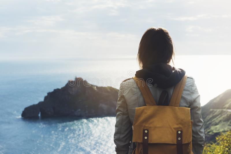 Hipster young girl with backpack enjoying sunset on seascape on peak mountain. Tourist traveler on background valley landscape. View mockup. Hiker looking stock images