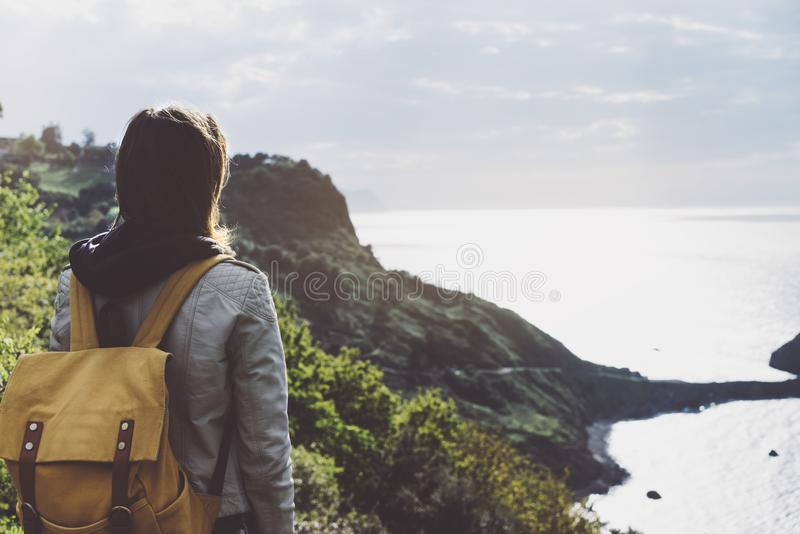 Hipster young girl with backpack enjoying sunset on seascape on peak mountain. Tourist traveler on background valley landscape. View mockup. Hiker looking stock image