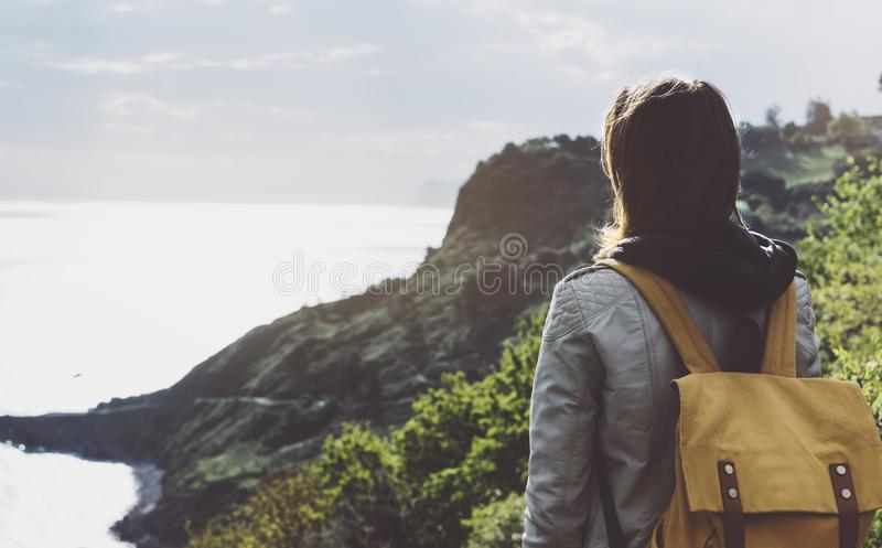 Hipster young girl with backpack enjoying sunset on seascape on peak mountain. Tourist traveler on background valley landscape. View mockup. Hiker looking royalty free stock image