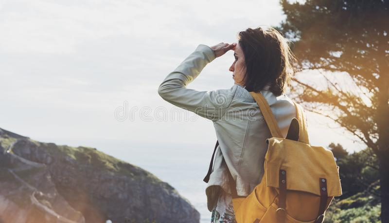 Hipster young girl with backpack enjoying sunset on seascape on peak mountain. Tourist traveler on background valley landscape. View mockup. Hiker looking royalty free stock photography