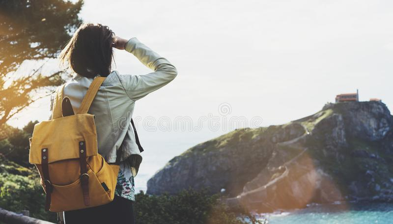 Hipster young girl with backpack enjoying sunset on seascape on peak mountain. Tourist traveler on background valley landscape. View mockup. Hiker looking stock photography