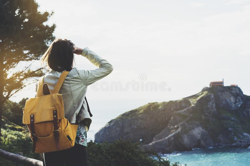 Hipster young girl with backpack enjoying sunset on seascape on peak mountain. Tourist traveler on background valley landscape. View mockup. Hiker looking stock photos