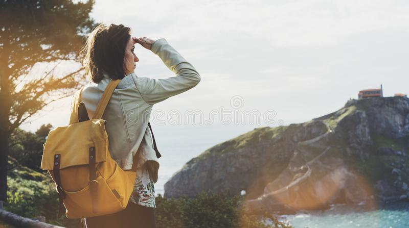 Hipster young girl with backpack enjoying sunset on seascape on peak mountain. Tourist traveler on background valley landscape stock image