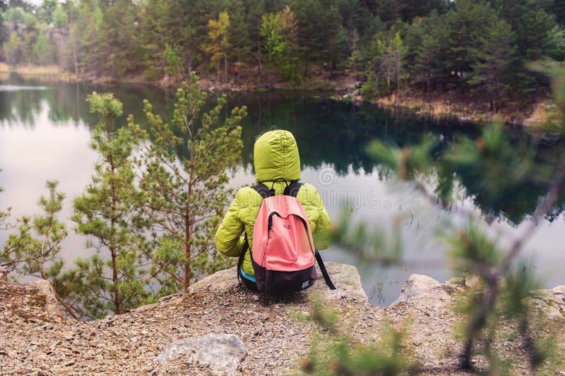 Hipster young girl with backpack enjoying the view of the lake. royalty free stock photos