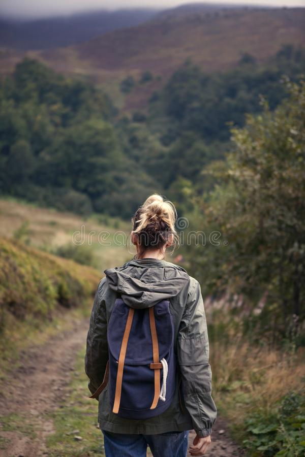 Hipster young girl with backpack hiking in the mountains royalty free stock photos