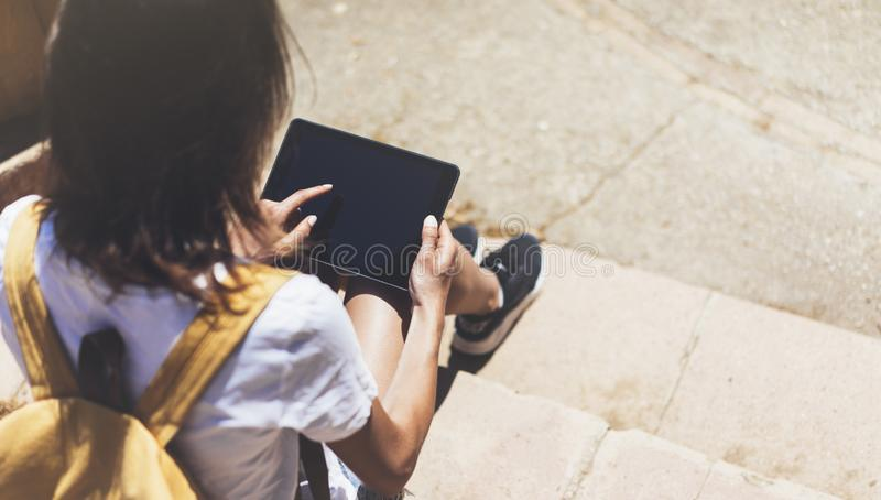 Hipster young girl with backpack using tablet computer camera, mockup of blank empty screen, holding gadget and planning travel royalty free stock image