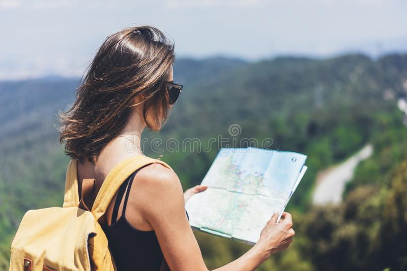 Hipster young girl with bright backpack enjoying panoramic mountain sea, using map and looking distance. Tourist traveler on back. Ground landscape Barcelona royalty free stock photo