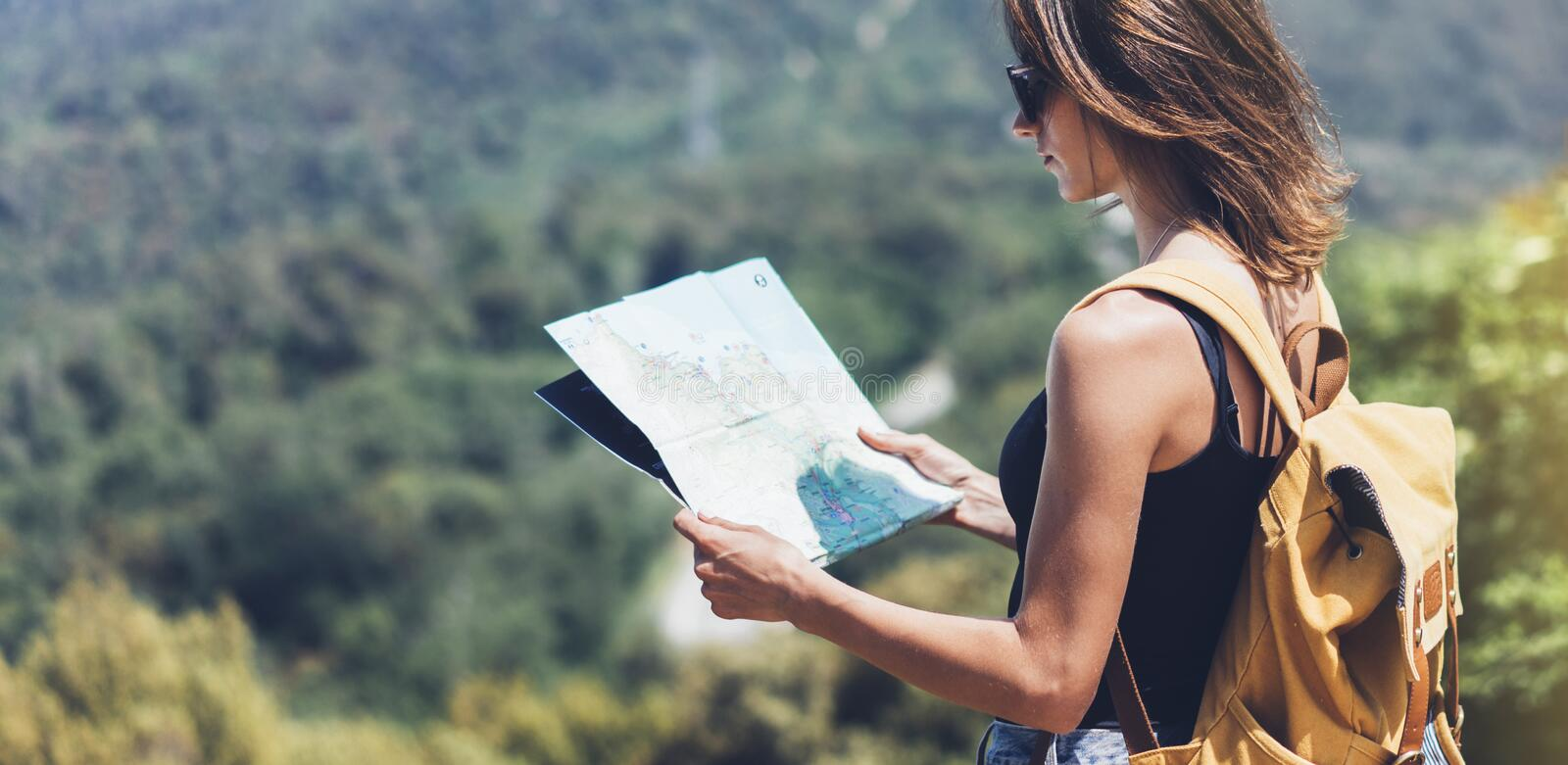 Hipster young girl with bright backpack enjoying panoramic mountain sea, using map and looking distance. Tourist traveler on back. Ground landscape Barcelona royalty free stock image