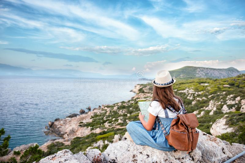 Hipster young girl with bright backpack enjoying panoramic mountain sea, using map and looking distance. Tourist traveler on stock image