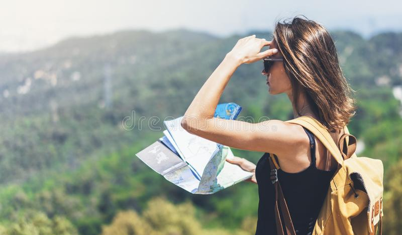 Hipster young girl with bright backpack enjoying panoramic mountain sea, using map and looking distance. Tourist traveler on back. Ground landscape Barcelona royalty free stock photography