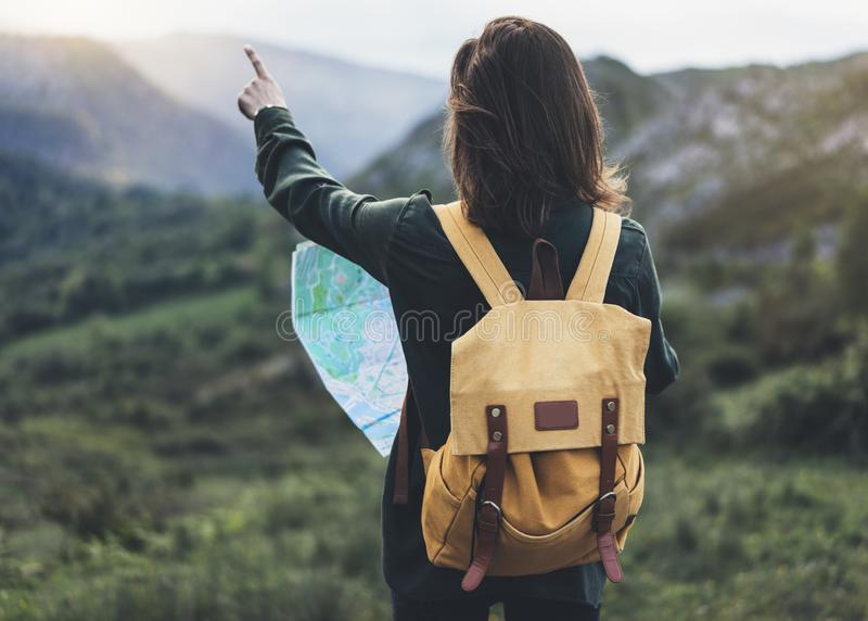 Hipster young girl with bright backpack enjoying sunset on peak of foggy mountain, looking a map and poining hand. Tourist travele stock photography