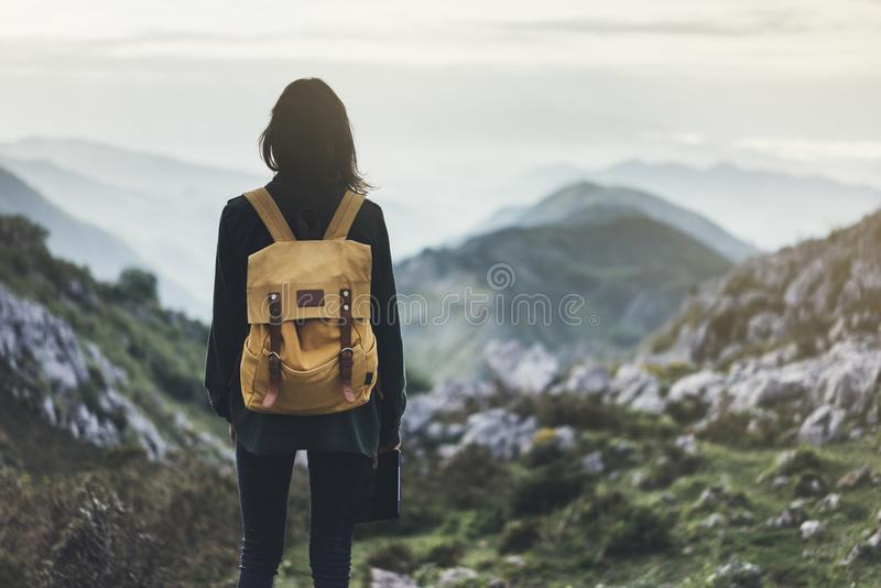 Hipster young girl with bright backpack enjoying sunset on peak of foggy mountain. Tourist traveler on background valley landscape. Panoramic view mockup. Hiker royalty free stock photography
