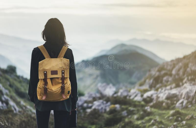 Hipster young girl with bright backpack enjoying sunset on peak of foggy mountain. Tourist traveler on background valley landscape. Panoramic view mockup. Hiker royalty free stock images