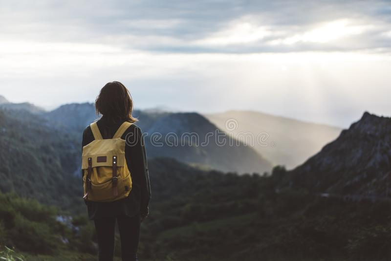 Hipster young girl with bright backpack enjoying sunset on peak of foggy mountain. Tourist traveler on background valley landscape. View mockup. Hiker looking royalty free stock photos