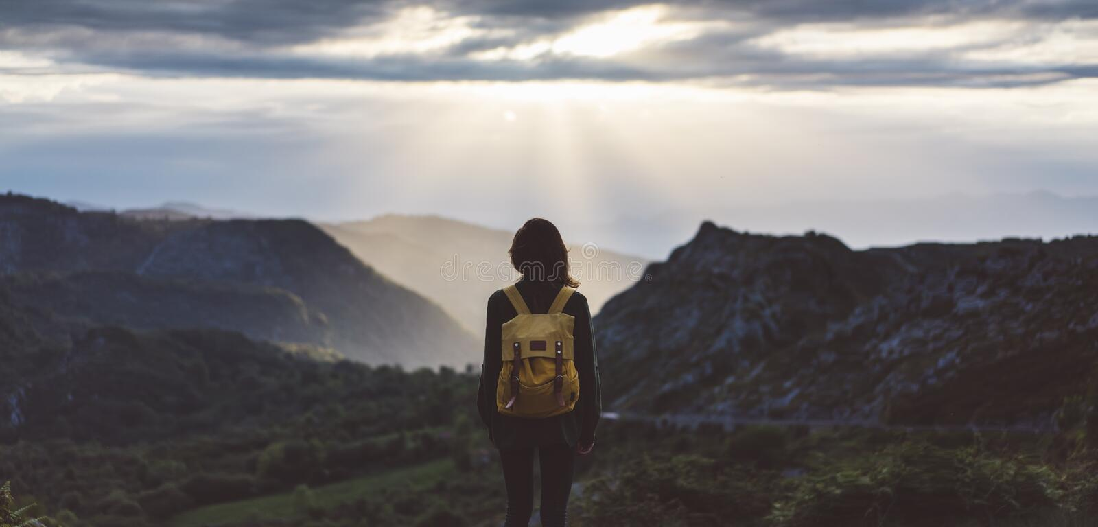 Hipster young girl with bright backpack enjoying sunset on peak of foggy mountain. Tourist traveler on background valley landscape. View mockup. Hiker looking stock photo