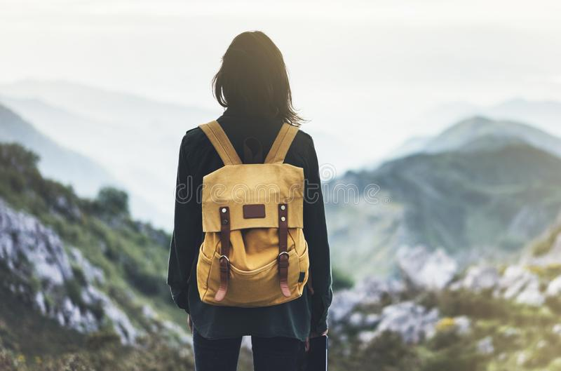 Hipster young girl with bright backpack enjoying sunset on peak of foggy mountain. Tourist traveler on background valley landscape. Panoramic view mockup. Hiker stock photo