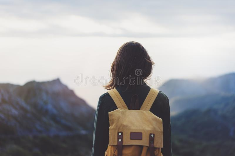 Hipster young girl with bright backpack enjoying sunset on peak of foggy mountain. Tourist traveler on background valley landscape. View mockup. Hiker looking royalty free stock images