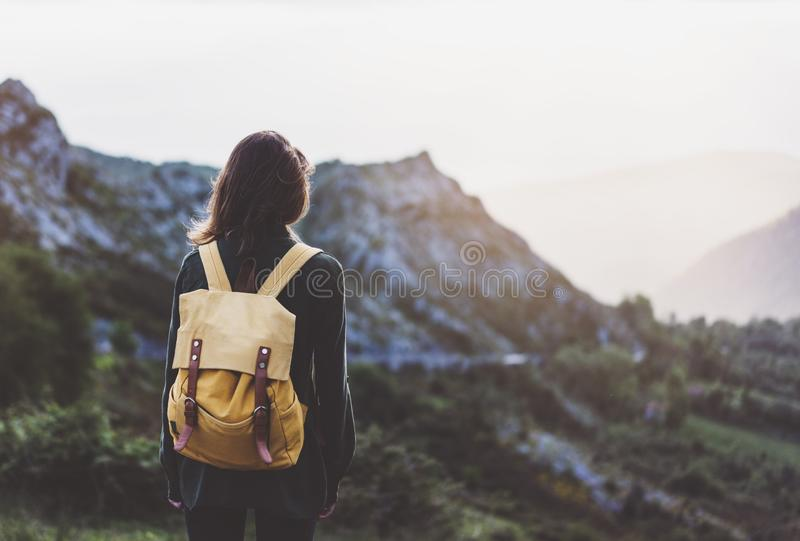 Hipster young girl with bright backpack enjoying sunset on peak of foggy mountain. Tourist traveler on background valley landscape. View mockup. Hiker looking royalty free stock photo
