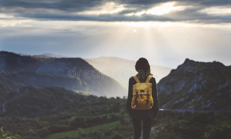 Hipster young girl with bright backpack enjoying sunset on peak of foggy mountain. Tourist traveler on background valley landscape. View mockup. Hiker looking royalty free stock photography