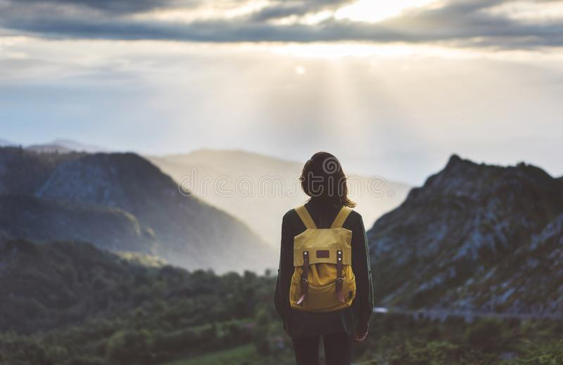 Hipster young girl with bright backpack enjoying sunset on peak of foggy mountain. Tourist traveler on background valley landscape. View mockup. Hiker looking stock images