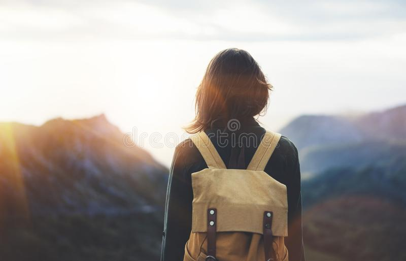 Hipster young girl with bright backpack enjoying sunset on peak of foggy mountain. Tourist traveler on background valley landscape. View mockup. Hiker looking royalty free stock image