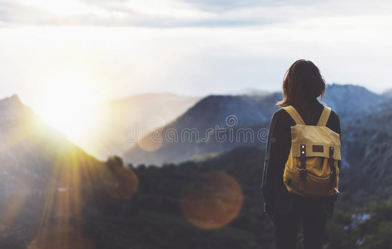 Hipster young girl with bright backpack enjoying sunset on peak of foggy mountain. Tourist traveler on background valley landscape. View mockup. Hiker looking stock image