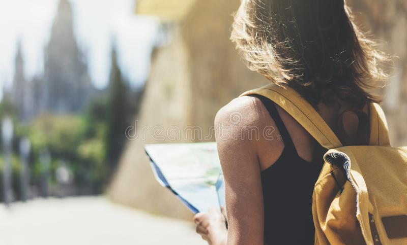 Hipster young girl with bright backpack and fashion sunglasses looking at map. Said view tourist traveler on background sun city. Person visiting the sights royalty free stock photo