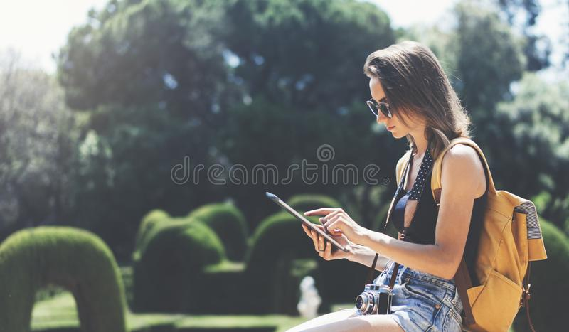 Hipster young girl with bright backpack and vintage camera using tablet or holding gadget, planning travel plan. View tourist royalty free stock images