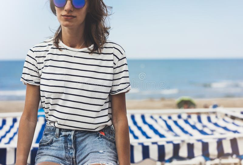 Hipster young girl with fashion sunglasses and striped t-shirt, sea look style concept. View model tourist traveler on background royalty free stock photos