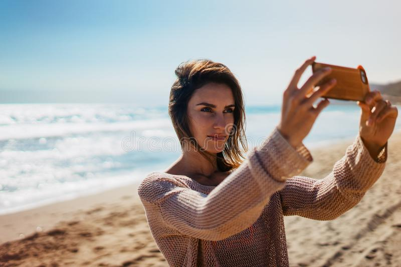 Hipster young girl photograph itself on smart phone gadget in sand coastline, blogger using in female hand mobile screen on backgr royalty free stock photography