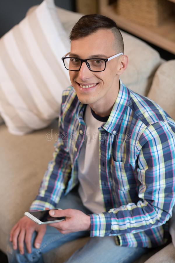 Hipster young male sitting on couch working on freelance. royalty free stock image
