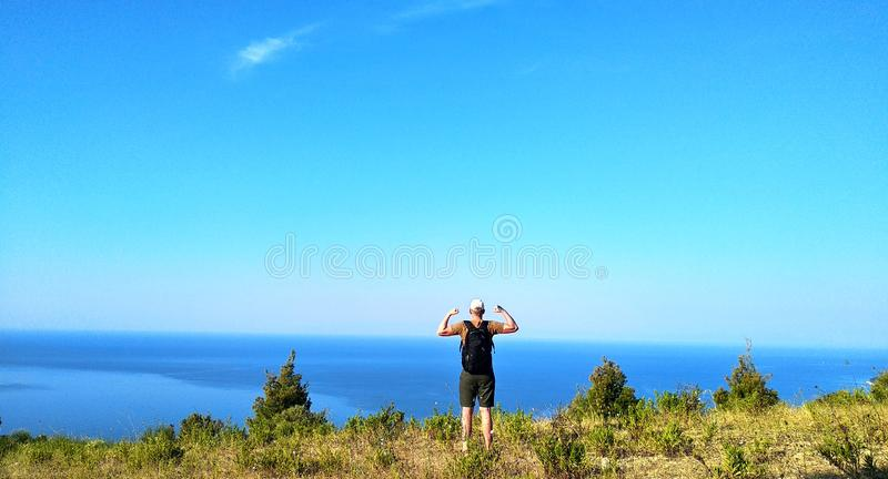 Hipster young man with backpack enjoying sunrise on peak of mountain. Male tourist traveler shows biceps after climbing mountain. On background scenery nature royalty free stock photo