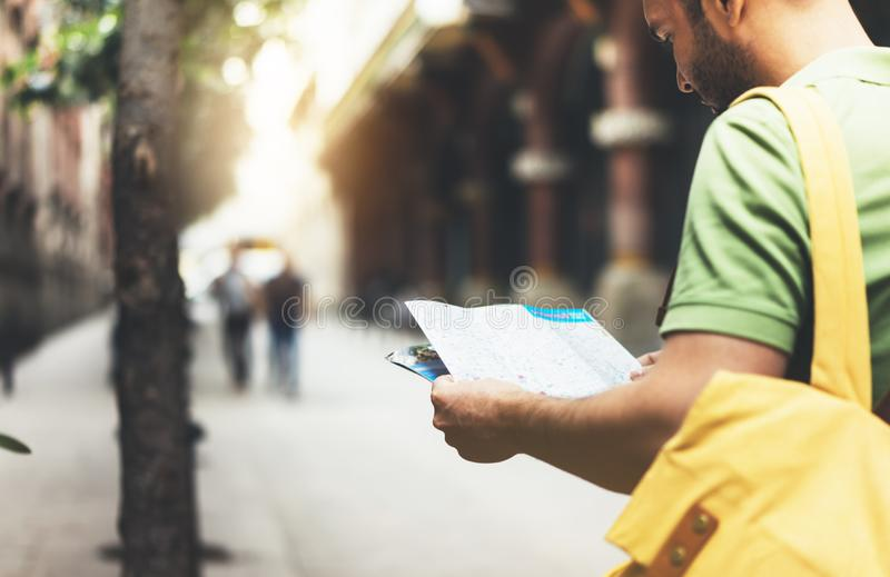 Hipster young man with backpack looking and holding map. Said view tourist traveler planning route on background sun city. Person royalty free stock photos