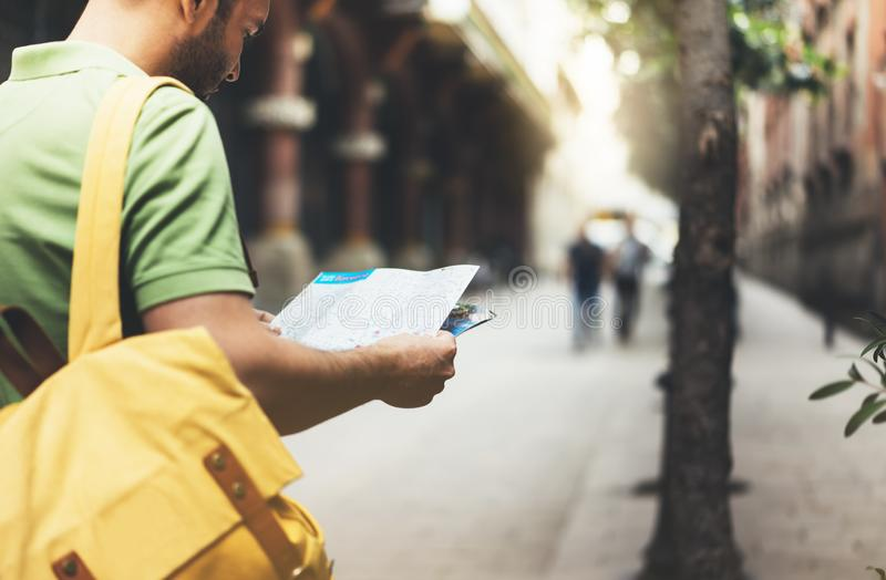 Hipster young man with backpack looking and holding map. Said view tourist traveler planning route on background sun city. Person stock photo