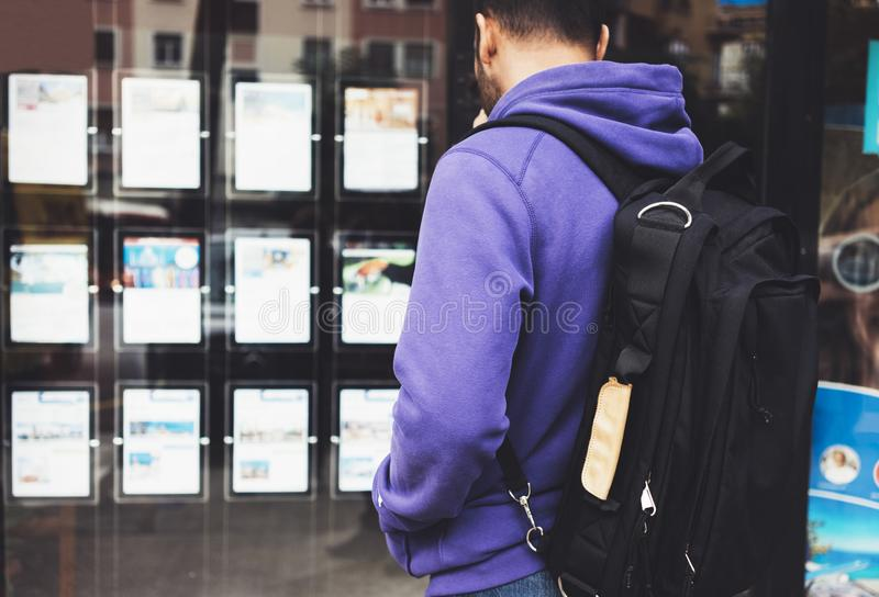 Hipster young man with backpack and map looking ad promo poster hotel choose apartments. Tourist traveler planning route royalty free stock photo