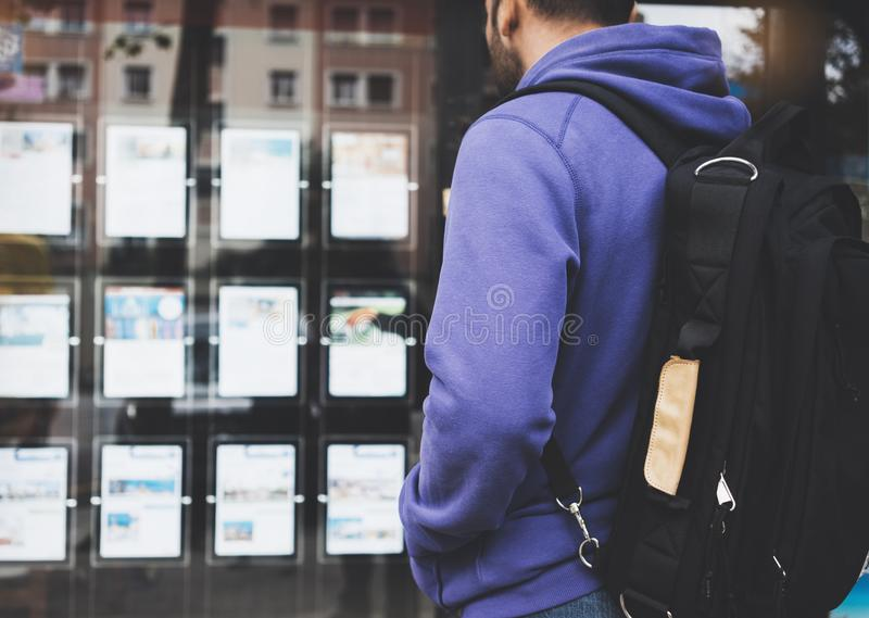 Hipster young man with backpack and map looking ad promo poster hotel choose apartments. Tourist traveler planning route on back royalty free stock image
