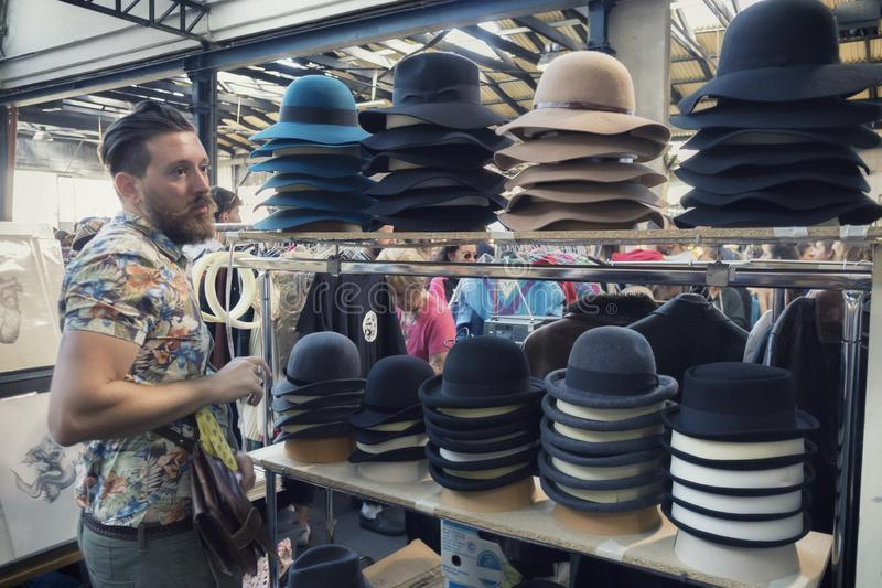 Hipster young man looking hats at East Market grand opening, the first marketplace in Milan whe royalty free stock photos