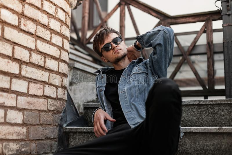 Hipster young man model in sunglasses in a blue denim jacket in black pants is resting on the stairs near a vintage brick wall stock photo