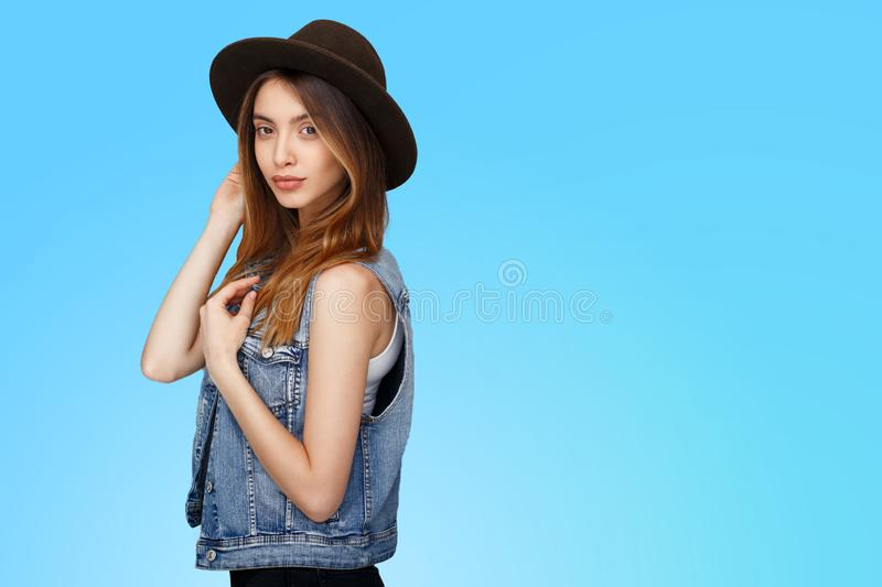 Hipster young woman in denim and hat, standing and looking at camera isolated over blue background. Copy space. royalty free stock photos