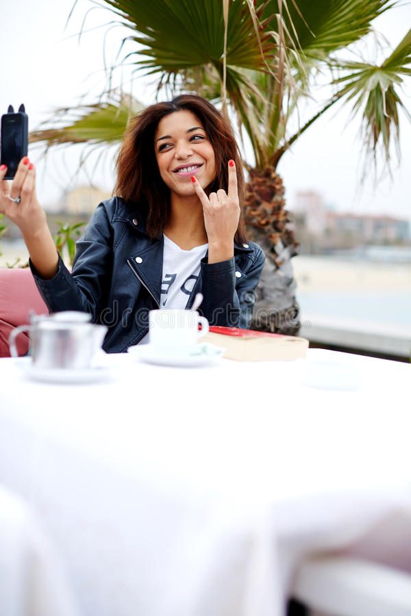 Hipster young woman taking a picture of herself on her cell phone looking playful. Afro american female taking fun self portrait with smartphone camera while stock photos