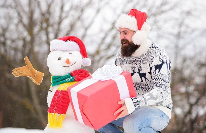 Hipster z pudełkiem na prezent od brody Koncepcja zaskoczenia Gry zimowe Aktywność zimowa Wakacje zimowe Człowiek zrobił śnieg zdjęcia royalty free