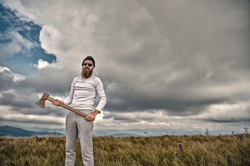 Hipster in zonnebril met bijltribune op berglandschap stock foto