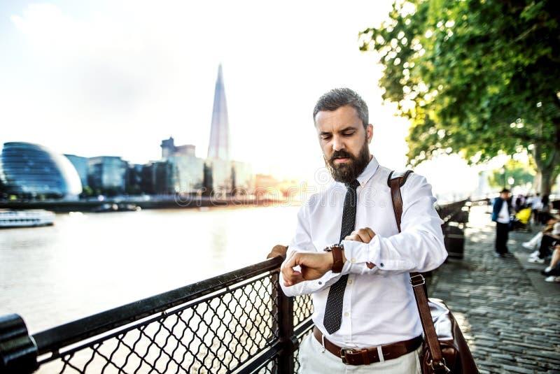 Hipsteraffärsman med bärbar datorpåsen som går vid floden i London som kontrollerar tiden royaltyfri fotografi