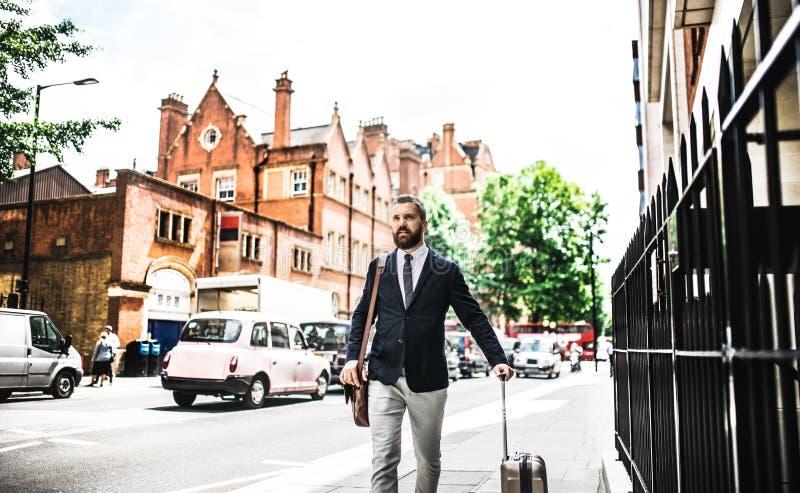 Hipsteraffärsman med resväskan som går ner gatan i London arkivbilder