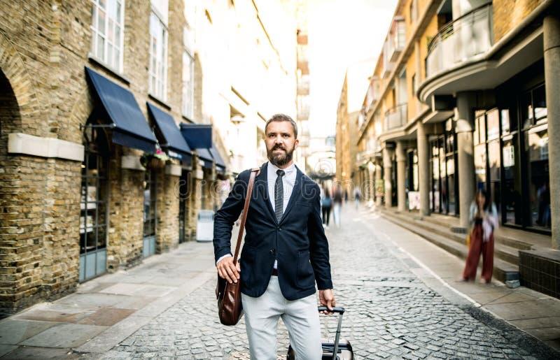 Hipsteraffärsman med resväskan som går ner gatan i London arkivbild