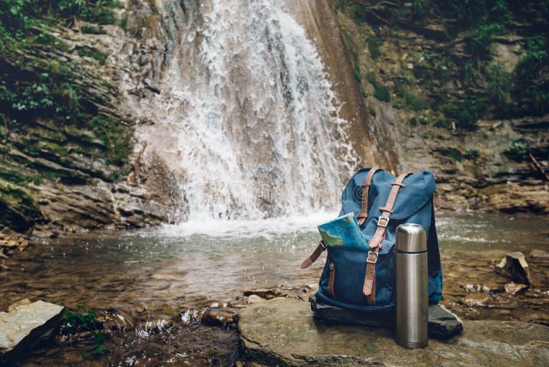 Hipsterblåttryggsäck, översikt och termos Sikt från Front Tourist Traveler Bag On vattenfallbakgrund Fotvandra för Wanderlast aff royaltyfri foto